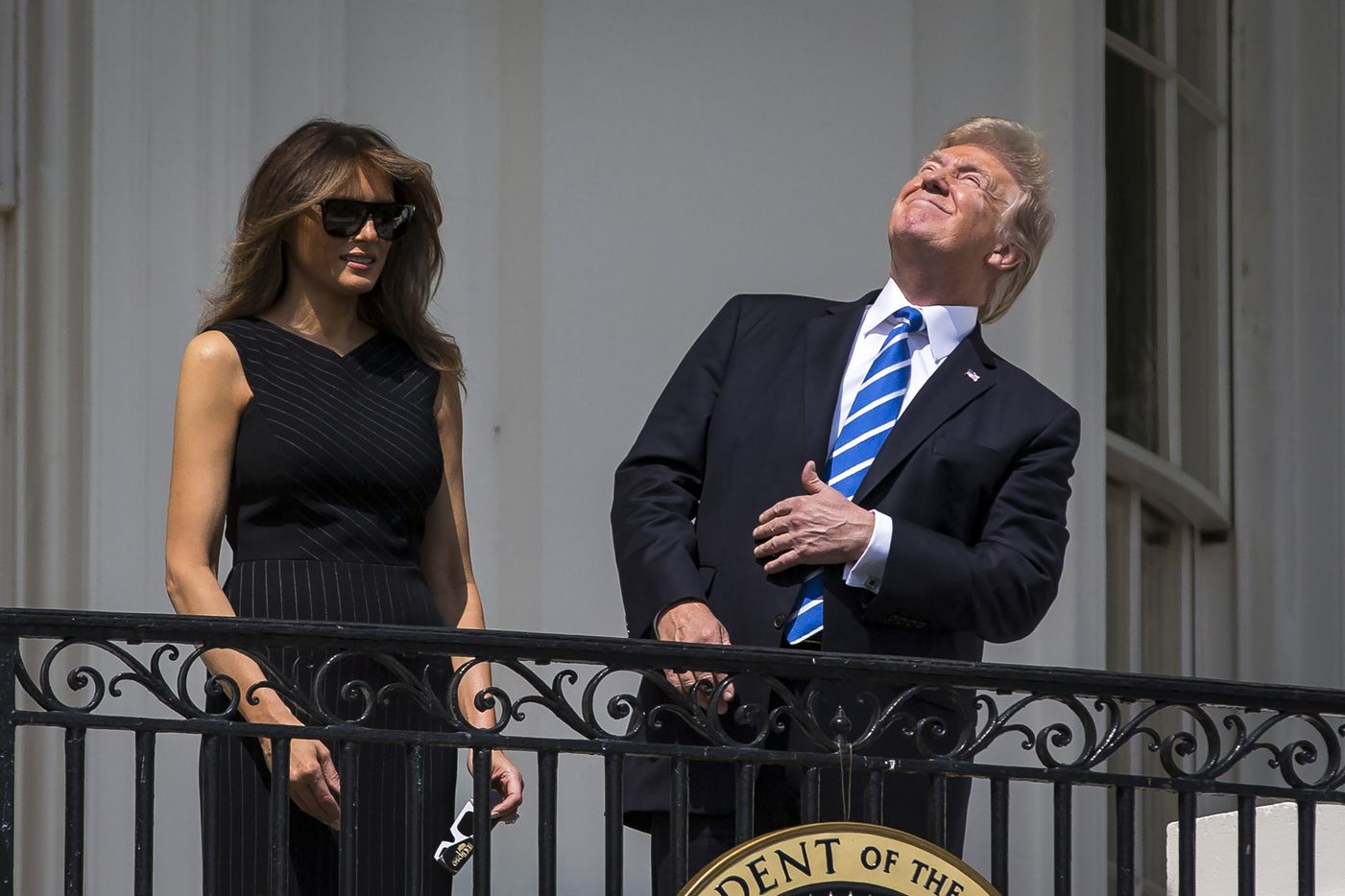 President Donald Trump and first lady Melania Trump view the solar eclipse from the Truman balcony of the White House.