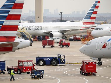 American Airlines crew members move luggage about as an aircraft is pushed back from the gate at Dallas-Fort Worth International Airport's Terminal C, Tuesday, January 21, 2020.
