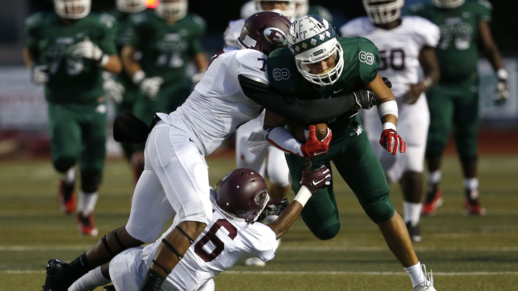 Ennis' Tori Williams (7) and Braylon Davis (16) tackle Waxahachie tight end Devan Brady (8) in the first quarter of the game between Waxahachie High School and Ennis High School at Lumpkins Stadium in Waxahachie, Texas on Sept. 11, 2015.