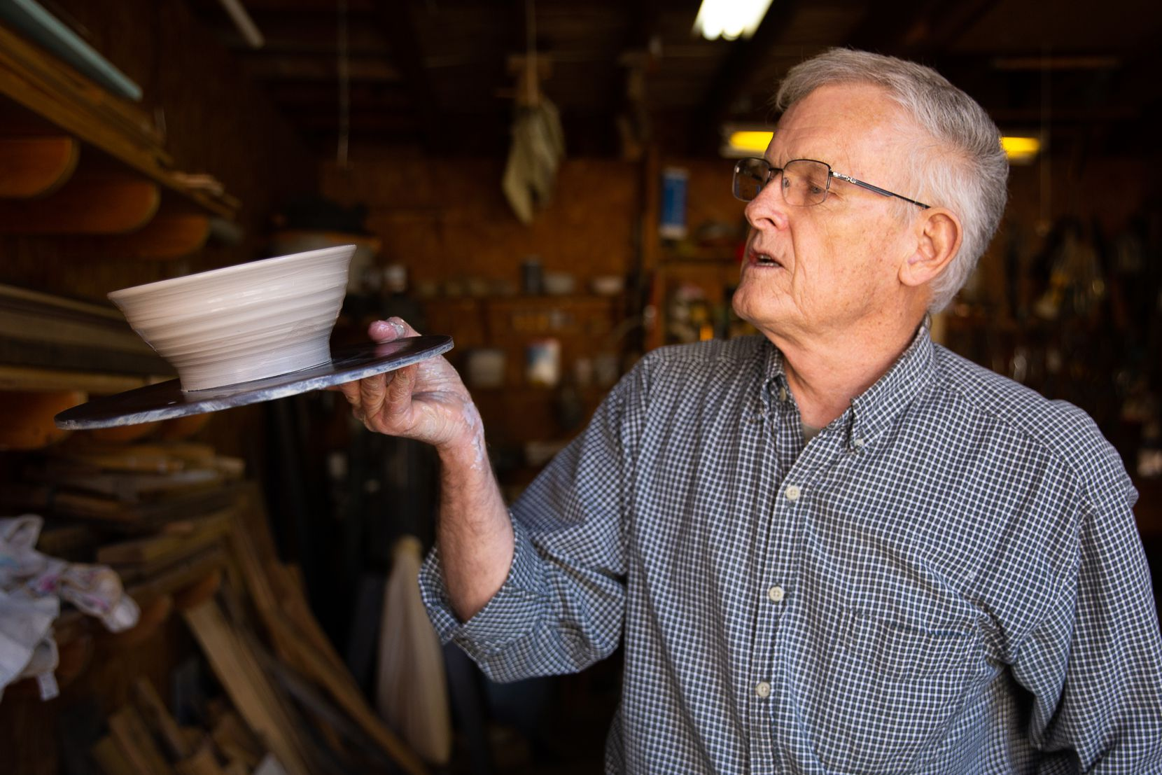 Bill Reed examines a bowl after shaping it in his garage workshop.