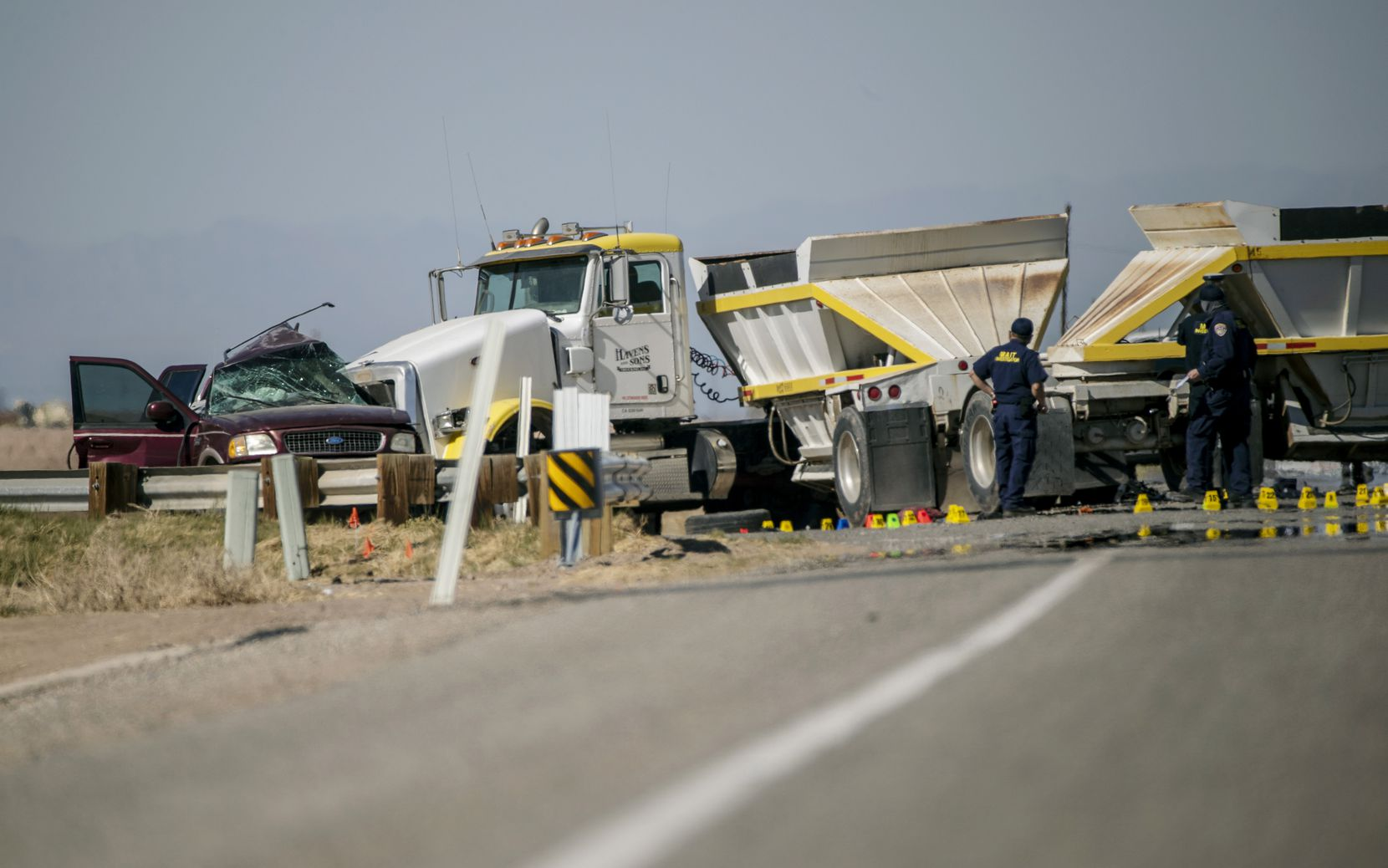 Police investigate the scene where an SUV carrying 25 people collided with a semi-truck, killing 13, on Highway 115 near the Mexican border on March 2, 2021 in Holtville, Calif.