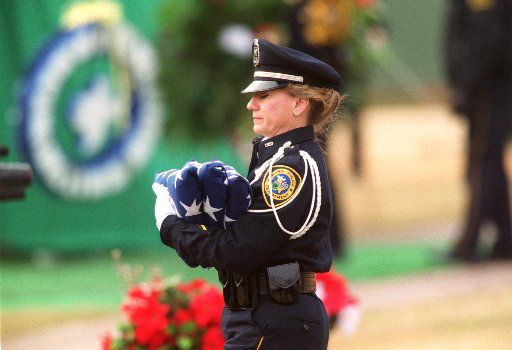 A police officer carried U.S. flags during the January 2001 funeral for Officer Aubrey Hawkins.