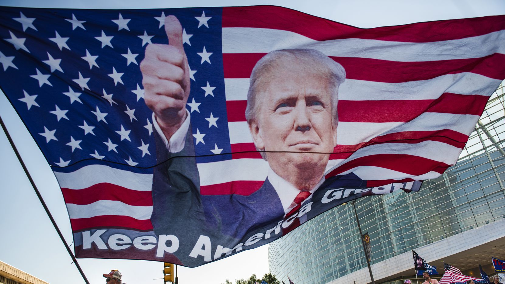 Randal Thom, 60, of Minnesota, waves an oversized flag of President Donald Trump outside the BOK Center in Tulsa, Okla., on June 19, 2020, the day before the president's first campaign rally since March 2.