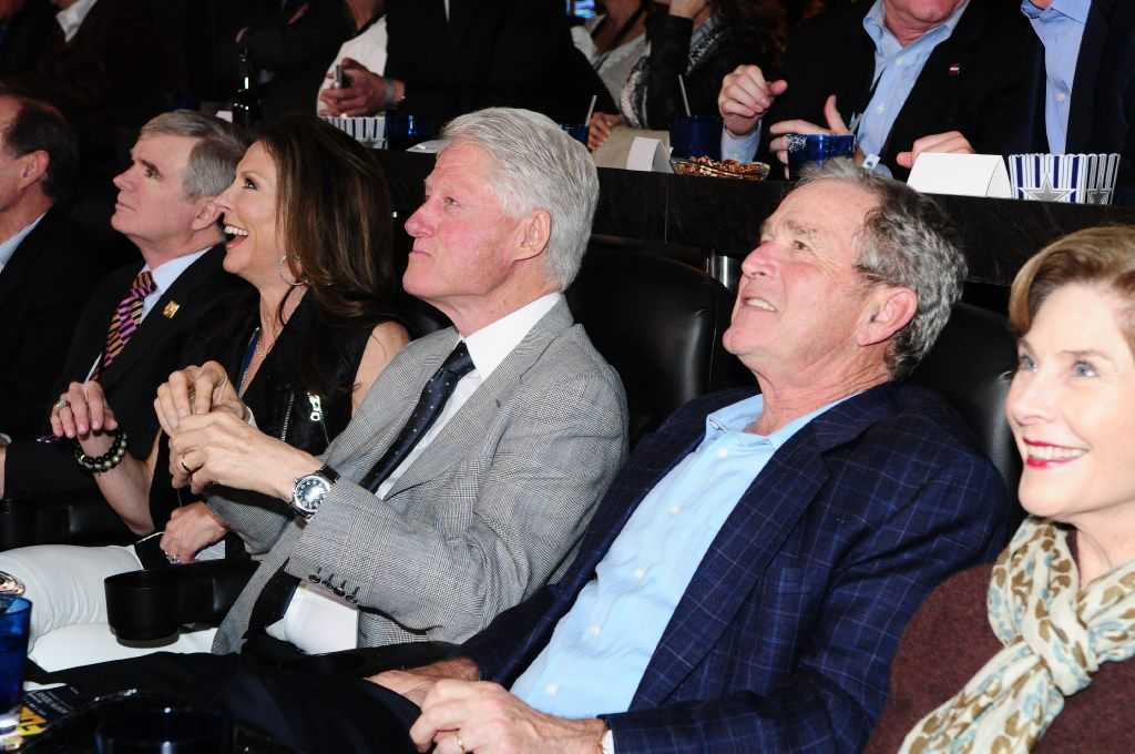 Presidents Bill Clinton and George W. Bush watch a Final Four game in Jerry Jones' suite at AT&T Stadium with Jones' daughter, Charlotte Anderson (left), and former first lady Laura Bush (right).