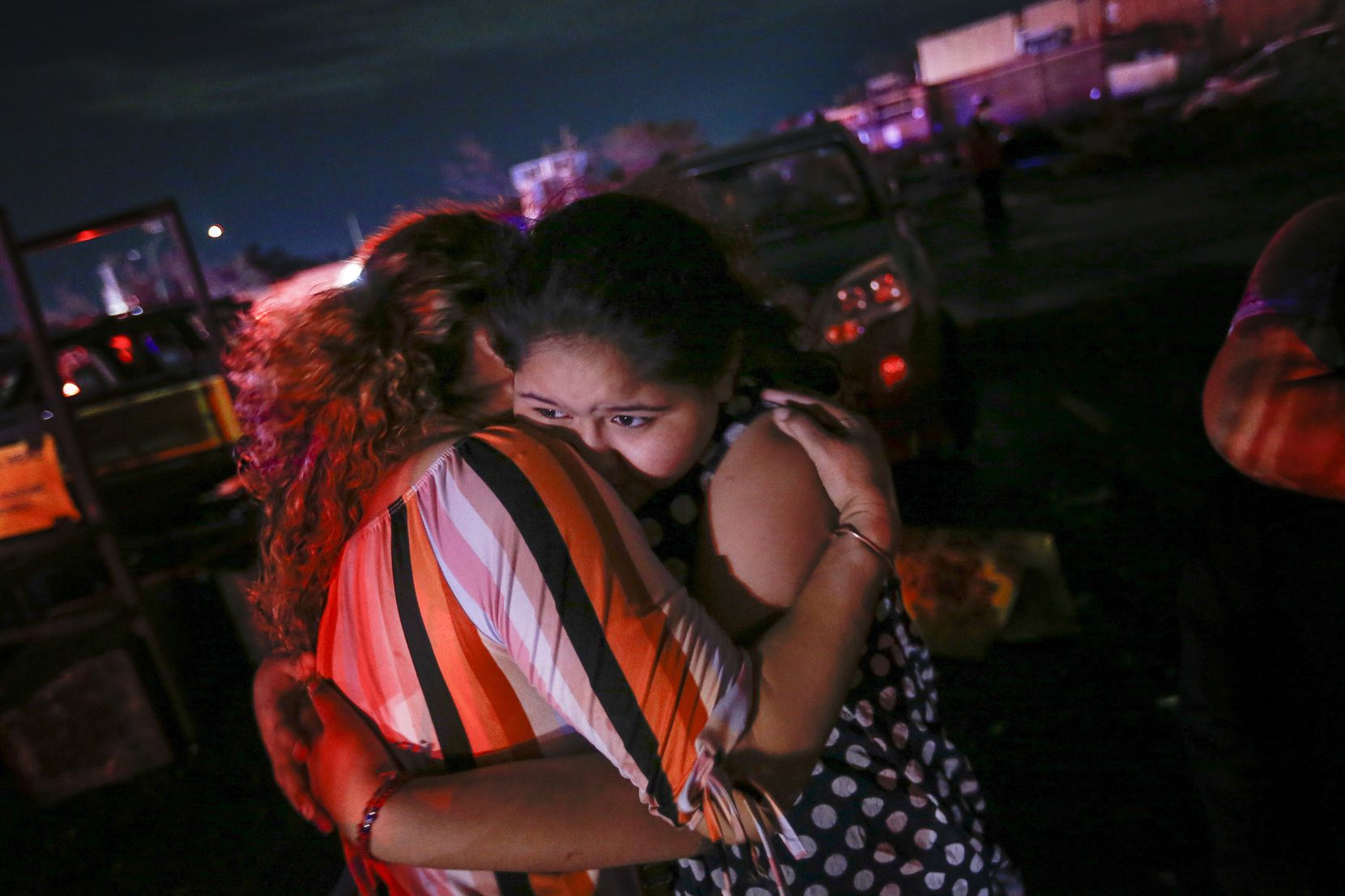 """Allisson Landeros, 11, hugs her aunt Maria Lara in the parking lot of a shopping center near the intersection of Walnut Hill Lane and Marsh Lane in Dallas where a storm hit Sunday, Oct. 20, 2019. Allisson was in the shopping center with other family members when the storm hit. """"We were measuring our dresses for tomorrow's picture day ... then all of the sudden we were in the middle of the storm ... and everything started collapsing,"""" she said.  (Ryan Michalesko/The Dallas Morning News)"""
