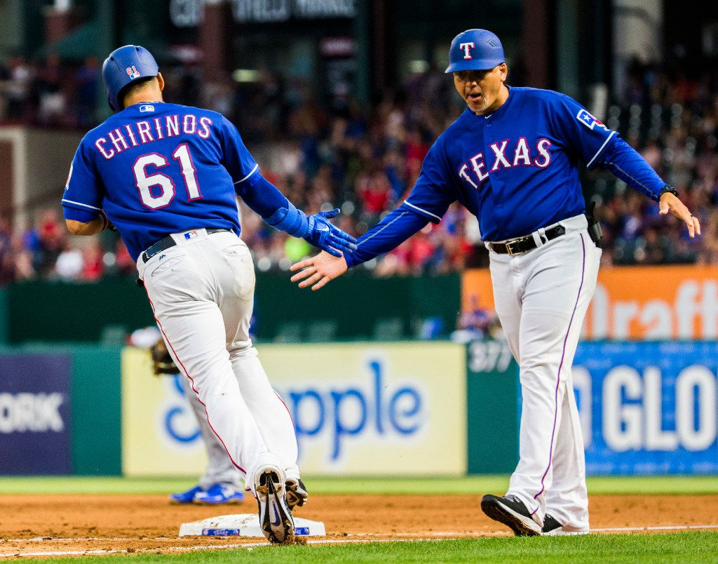 Texas Rangers catcher Robinson Chirinos (61) high-fives first base coach Hector Ortiz (4) after hitting a home run during the first inning of an MLB game between the Texas Rangers and the Kansas City Royals on Friday, April 21, 2017 at Globe Life Park in Arlington, Texas.