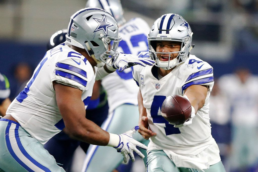 Dallas Cowboys quarterback Dak Prescott (4) hands the ball off to Dallas Cowboys running back Ezekiel Elliott (21) during the second half of play at AT&T Stadium in Arlington, Texas on Sunday, December 24, 2017. Dallas Cowboys lost to the Seattle Seahawks 21-12. (Vernon Bryant/The Dallas Morning News)