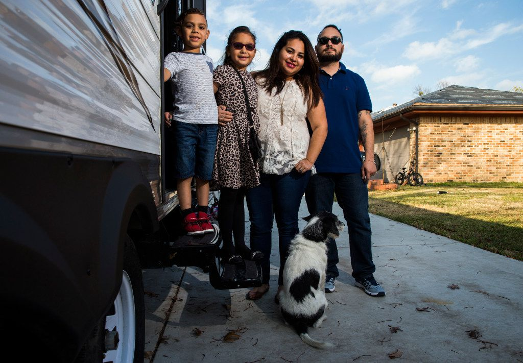 Sebastian Vega, 5, Trinity Vega, 7, Jenny Vega and Alex Vega pose for a portrait outside a trailer, which is parked in the driveway of their home, right, on Kelso Lane in Garland, Texas. They believe their insurance company was not offering them an adequate amount to pay for repairs after their house was severely damaged by a tornado on Dec. 26, 2015. The Vegas have been living in a trailer since March, while they await mediation.