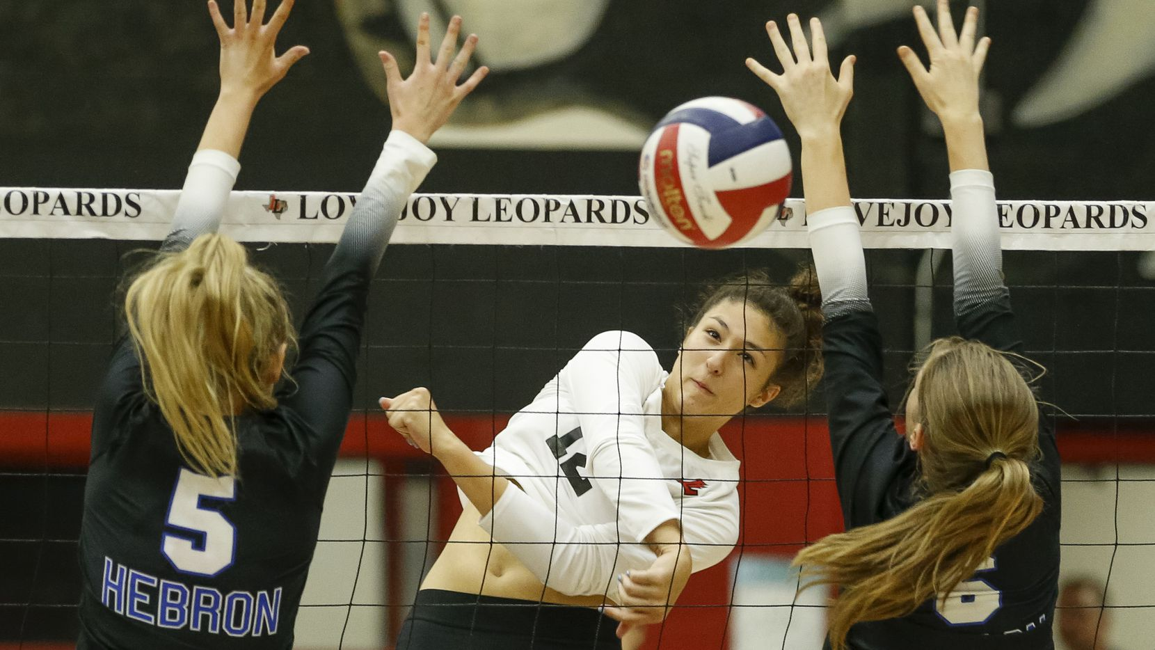 Lovejoy's Hannah Gonzalez (12) spikes the ball between Hebron's Hannah Redrow (5) and Sophie Hoke (6) during Lovejoy's 25-13, 25-11, 25-16 win Tuesday. Lovejoy is No. 2 in this week's Class 5A-others area rankings, and Hebron is ranked No. 7 in 6A. (Elias Valverde II/The Dallas Morning News)