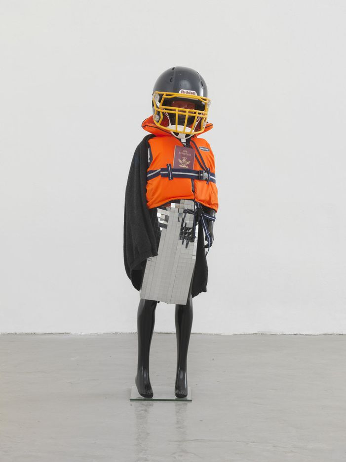 Schauspieler II, 8 2014 by German artist Isa Genzken; black child mannequin on glass stand, life jacket, silver mirror foil, passport, woolen jumper, American football helmet, spray paint;