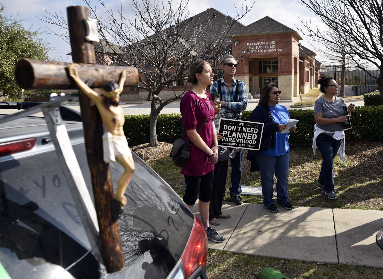 Anna Marinceo, 20, (left) of Flower Mound sang hymns Saturday outside of the Planned Parenthood South Dallas Surgical Health Services Center.