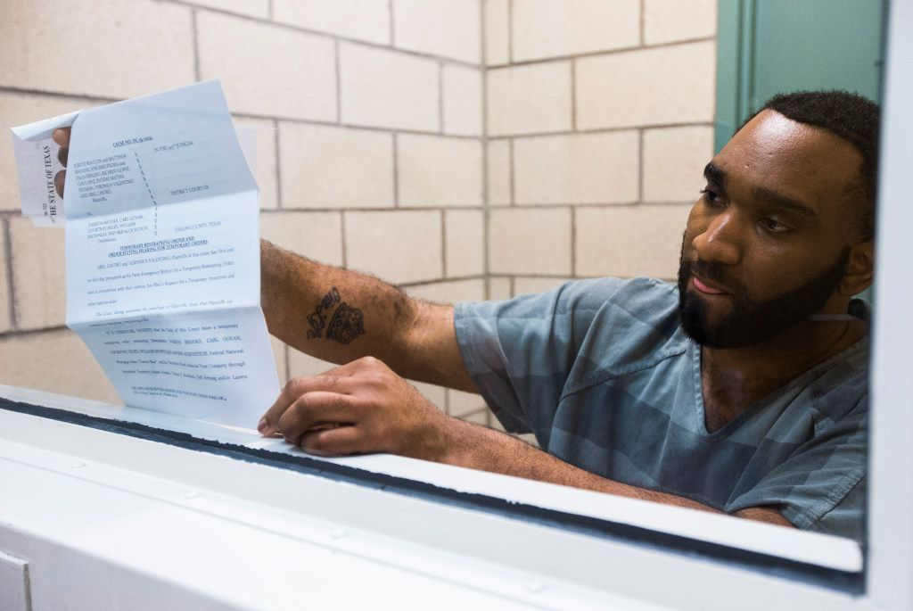 Carl Govan holds up documents on his case on Aug. 2, 2017, at the Dallas County Jail. Govan is accused of scamming several families in to buying homes that he didn't have the right to sell.