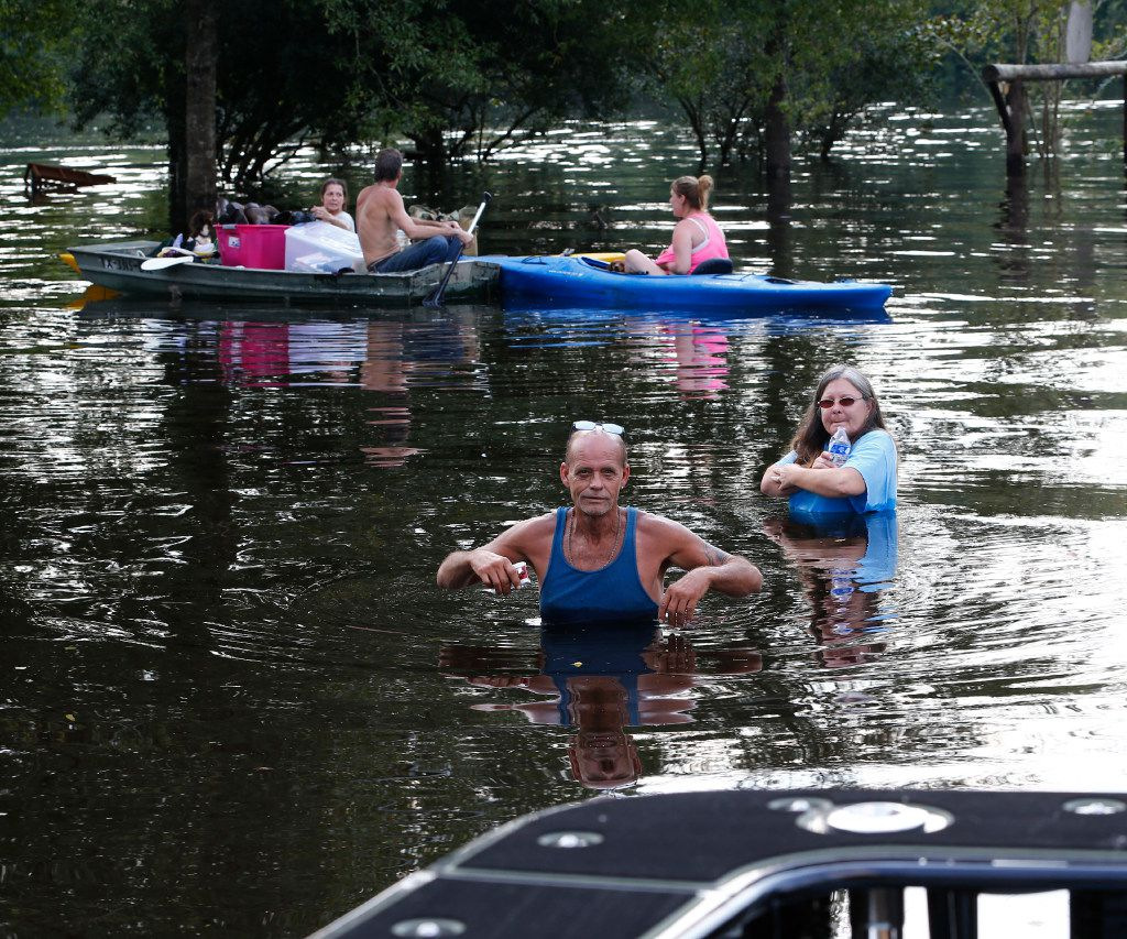 Ronnie Hare and Patricia Conwaywalk in the flooded water to an airboat after her boat was stranded after Hurricane Harvey in Vidor, Texas, on Sept. 3, 2017.