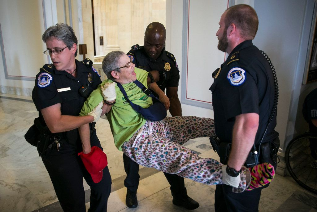 A demonstrator is removed from outside of the offices of Senate Majority Leader Mitch McConnell (R-Ky.), as several gathered to protest Medicaid cuts, on Capitol Hill, in Washington, June 22, 2017. Senate Republicans, who have promised a repeal of the Affordable Care Act for seven years, took a major step Thursday toward that goal, unveiling a bill to cut Medicaid deeply and end the health law's mandate that most Americans have health insurance. (Al Drago/The New York Times)