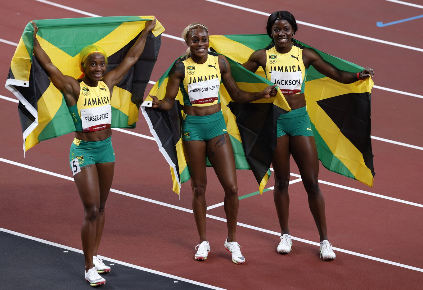 Jamaica's Shelly-Ann Fraser-Pryce, Elaine Thompson-Herah and Shericka Jackson hold up the Jamaican flag after taking first, second, and third in the women's 100 meter final race during the postponed 2020 Tokyo Olympics at Olympic Stadium, on Saturday, July 31, 2021, in Tokyo, Japan. Thompson Herah broke the Olympic record with a time of 10.61 to earn a gold medal. (Vernon Bryant/The Dallas Morning News)