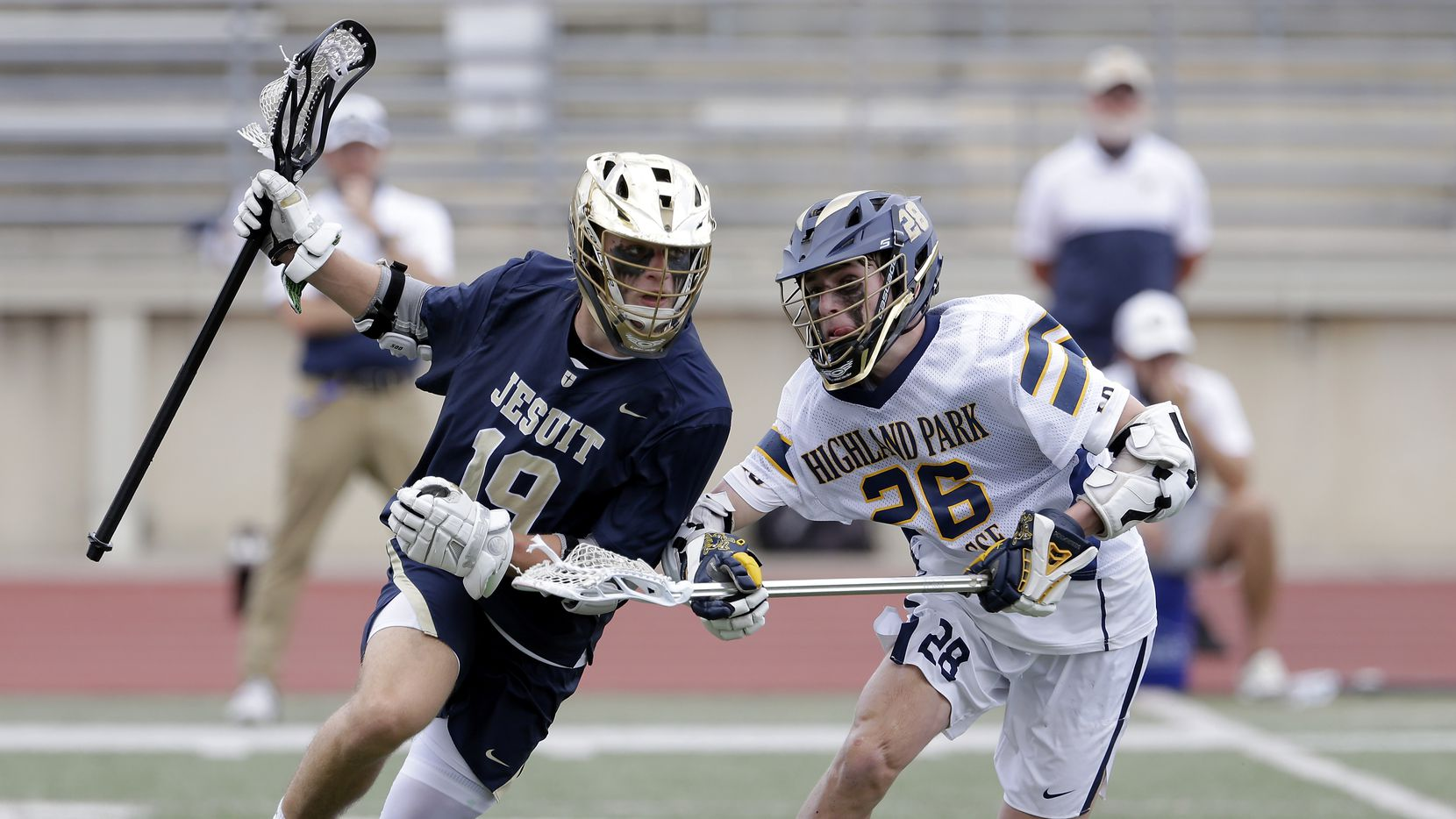 Dallas Jesuit's Caiden Vlasimsky (19) is stick checked by Highland Park's Rhodes Crow (26) during the Class AA Texas High School Lacrosse League State Championship game held at George Turner Stadium in Humble, Texas on Sunday, May 9, 2021.