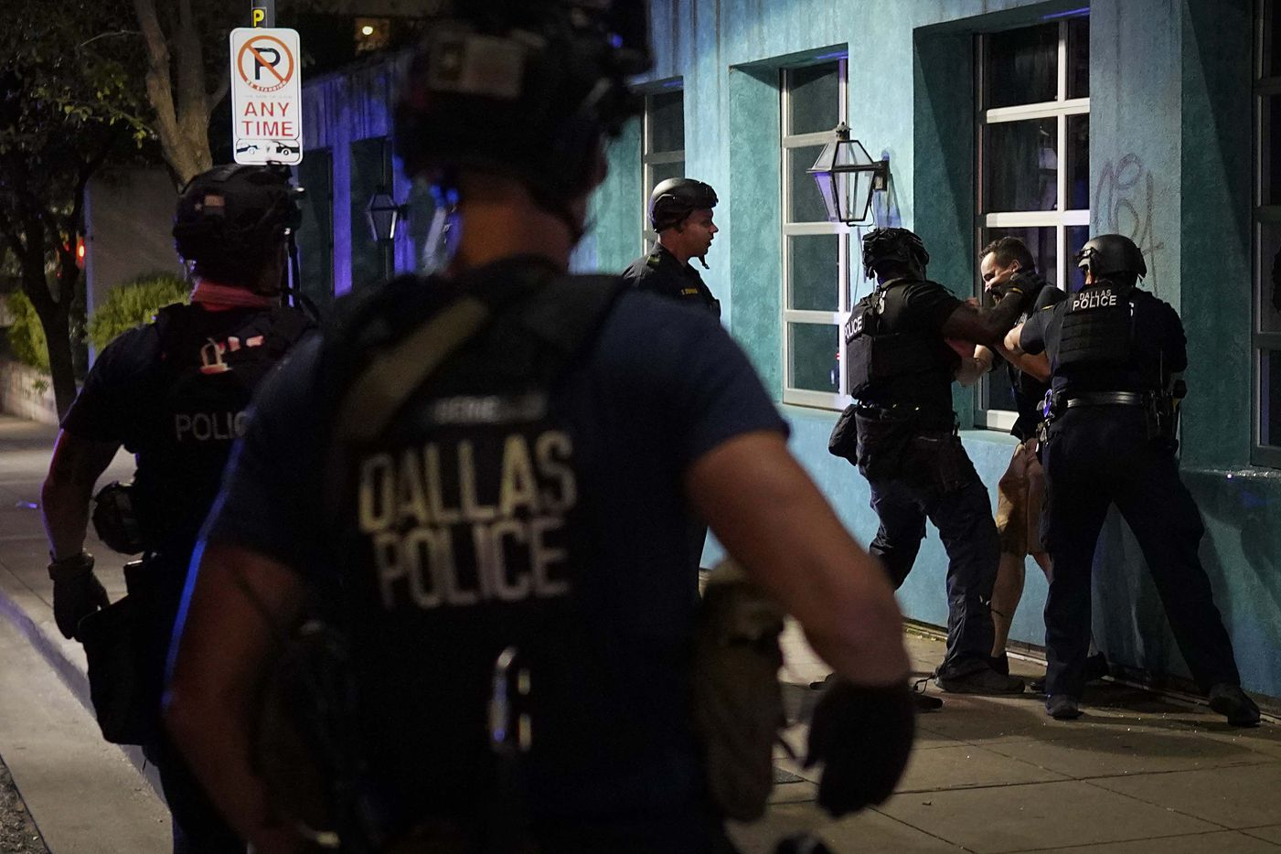 Dallas police arrest a man at Main Street and St. Paul as they go block by block working to clear groups of people from downtown streets following a protest against police brutality in the early morning hours of Saturday, May 30, 2020, in Dallas.