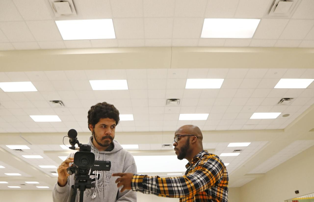 Justin Baylor, a teacher and alumnus of DeSoto High School (right), talks to Nicolas Contreras about framing his shots while producing a student movie at DeSoto High School.