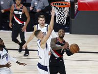 Portland Trail Blazers guard Damian Lillard (0) shoots while Dallas Mavericks forward Kristaps Porzingis (6) defends during the second half of an NBA basketball game Tuesday, Aug. 11, 2020, in Lake Buena Vista, Fla.