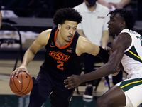 Oklahoma State guard Cade Cunningham (2) drives the ball against Baylor forward Jonathan Tchamwa Tchatchoua (23) in the second half of an NCAA college basketball game, Thursday, March 4, 2021, in Waco, Texas.