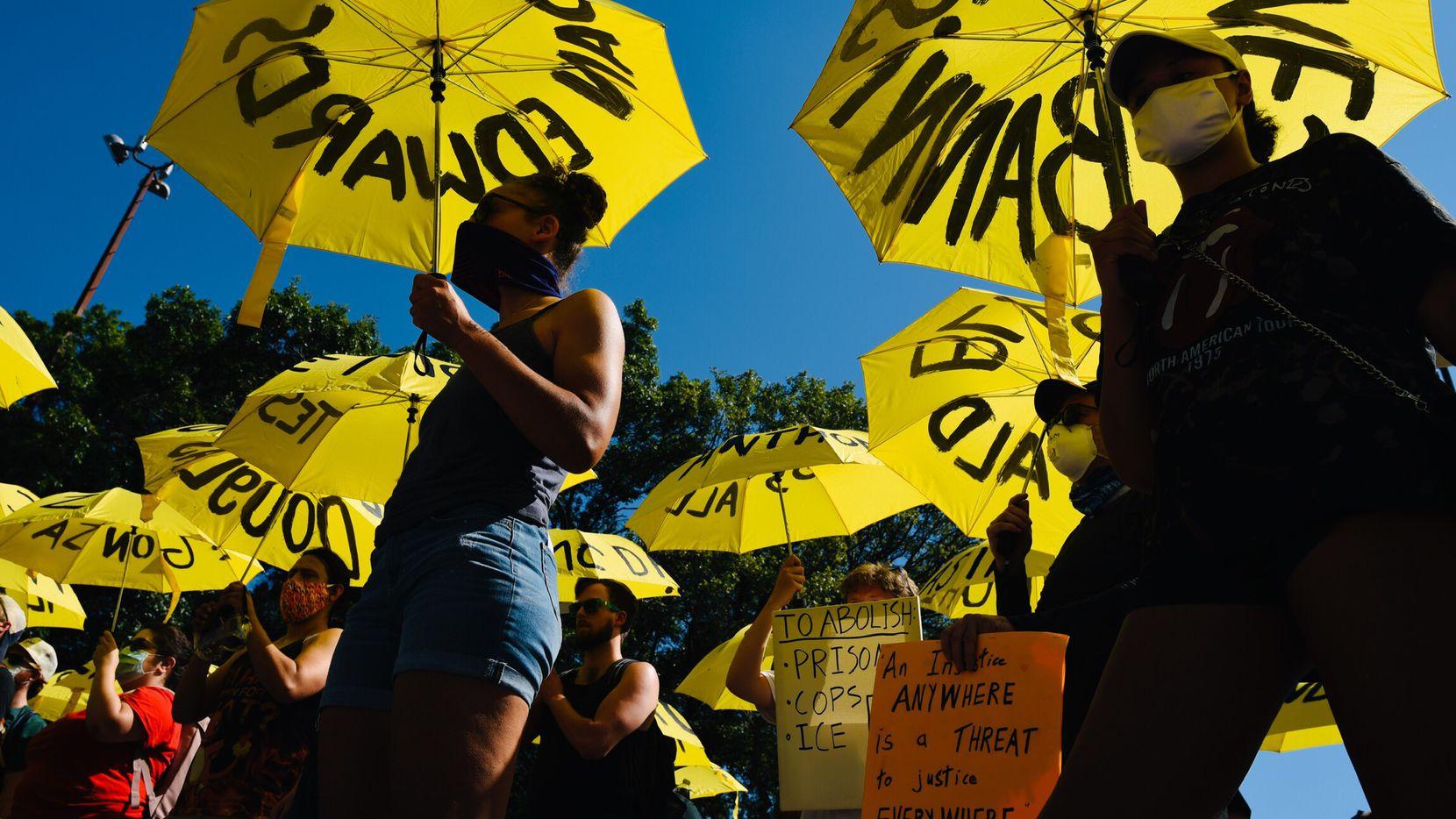 Una marcha de sombrillas amarillas con los nombres de las víctimas de la violencia policial arrancó desde Reverchon Park, donde hay un monumento que recuerda la muerte de Santos Rodríguez a manos de un policía.