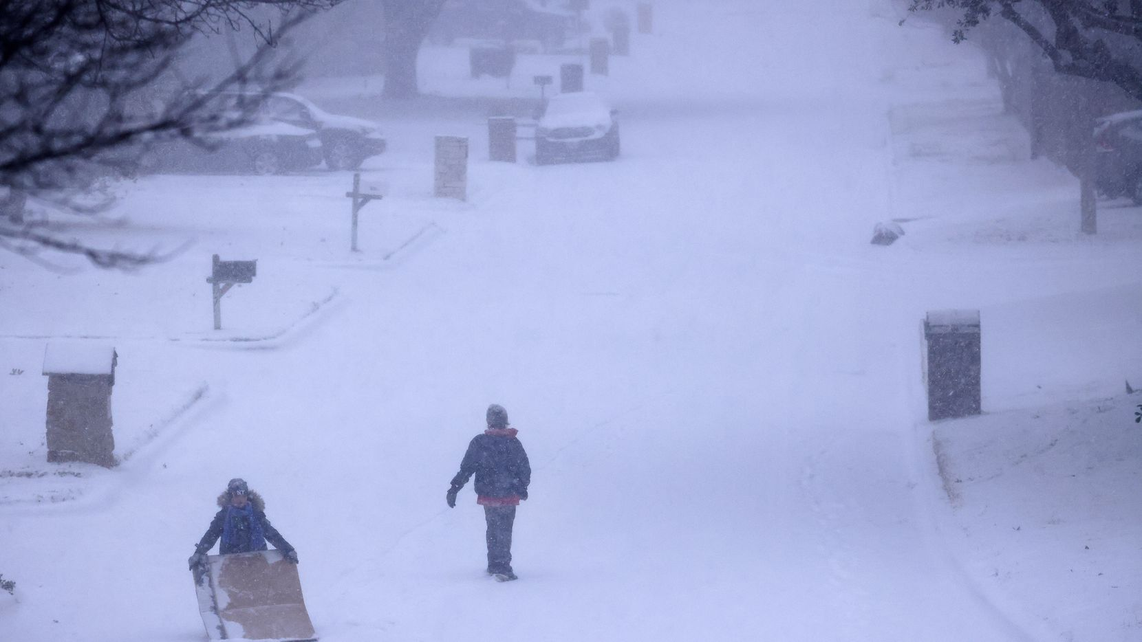 Kids improvised by sledding on large pieces of cardboard down a steep, snow-covered street in North Arlington on Sunday.