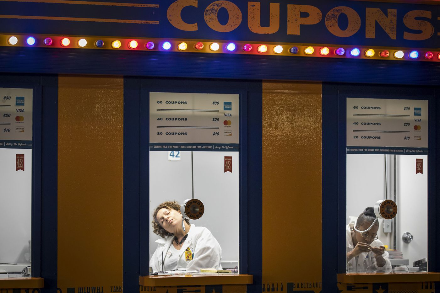 With no guests in sight close to 10 p.m., Brandy Mosley, 42, dozes off while waiting in her coupon booth for the end of her 12-hour shift, after the entrance gates had closed. On weeknights the fair entrance gates close at 9 p.m. but the ticket booths and Midway remain open for a short time until guests already inside finish their nights or are asked to leave so the fairgrounds can shut down.