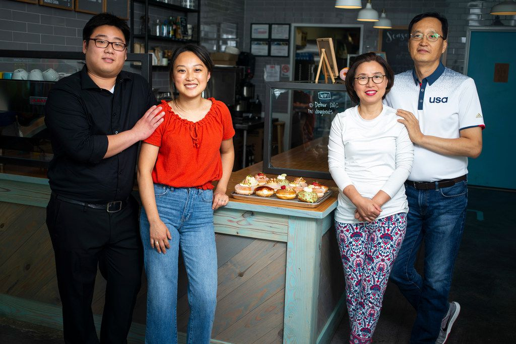 KJ Park (left) poses for a photograph with his wife, Jinny Cho, owner of Detour Doughnuts and Coffee, his mother-in-law,  Miran Han, and father-in-law Gab Kyu Cho, right, at Detour Doughnuts and Coffee in Frisco.