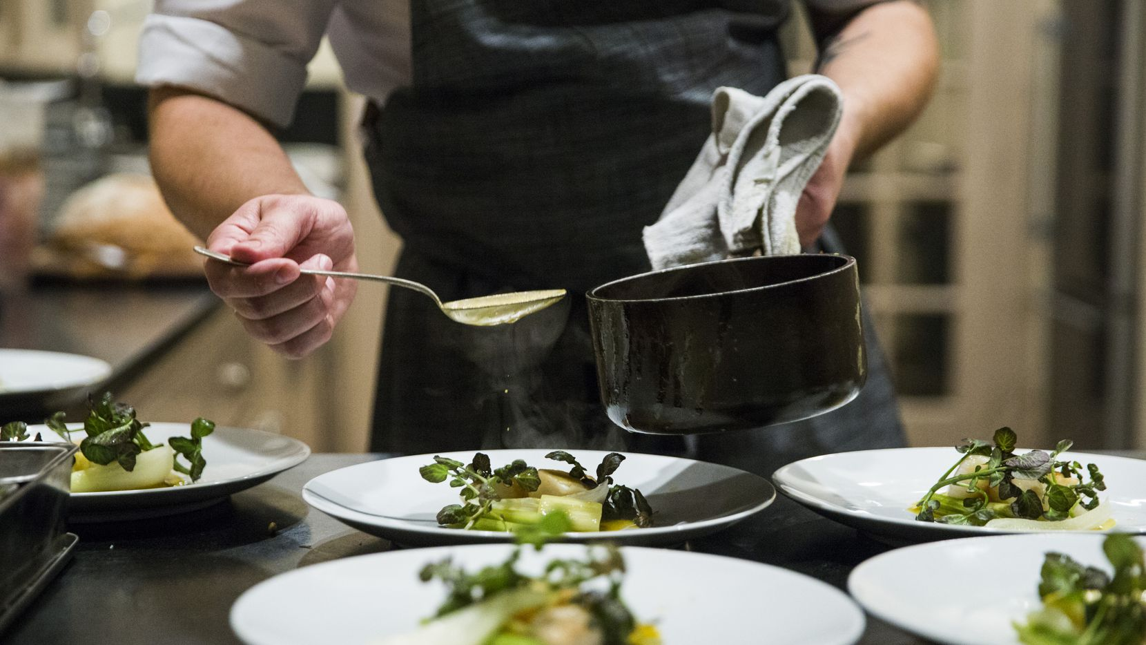 Chef Casey La Rue plates seared scallops with spring onion, fennel and crab reduction as he hosts a pop-up dinner at an Airbnb in Dallas on Saturday, Jan. 25, 2020.