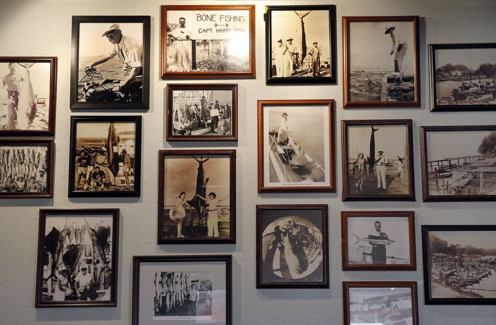 Old fishing photos cover a wall at 20 Feet Seafood on Peavy Rd. in Dallas, Tuesday, September 17, 2019.