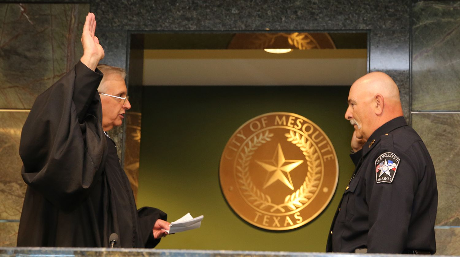 Mesquite Municipal Judge Steve Crane swears in City Marshal Michael Meek in a 2015 photo. Crane announced this week that he plans to retire in November after more than a decade in his role.