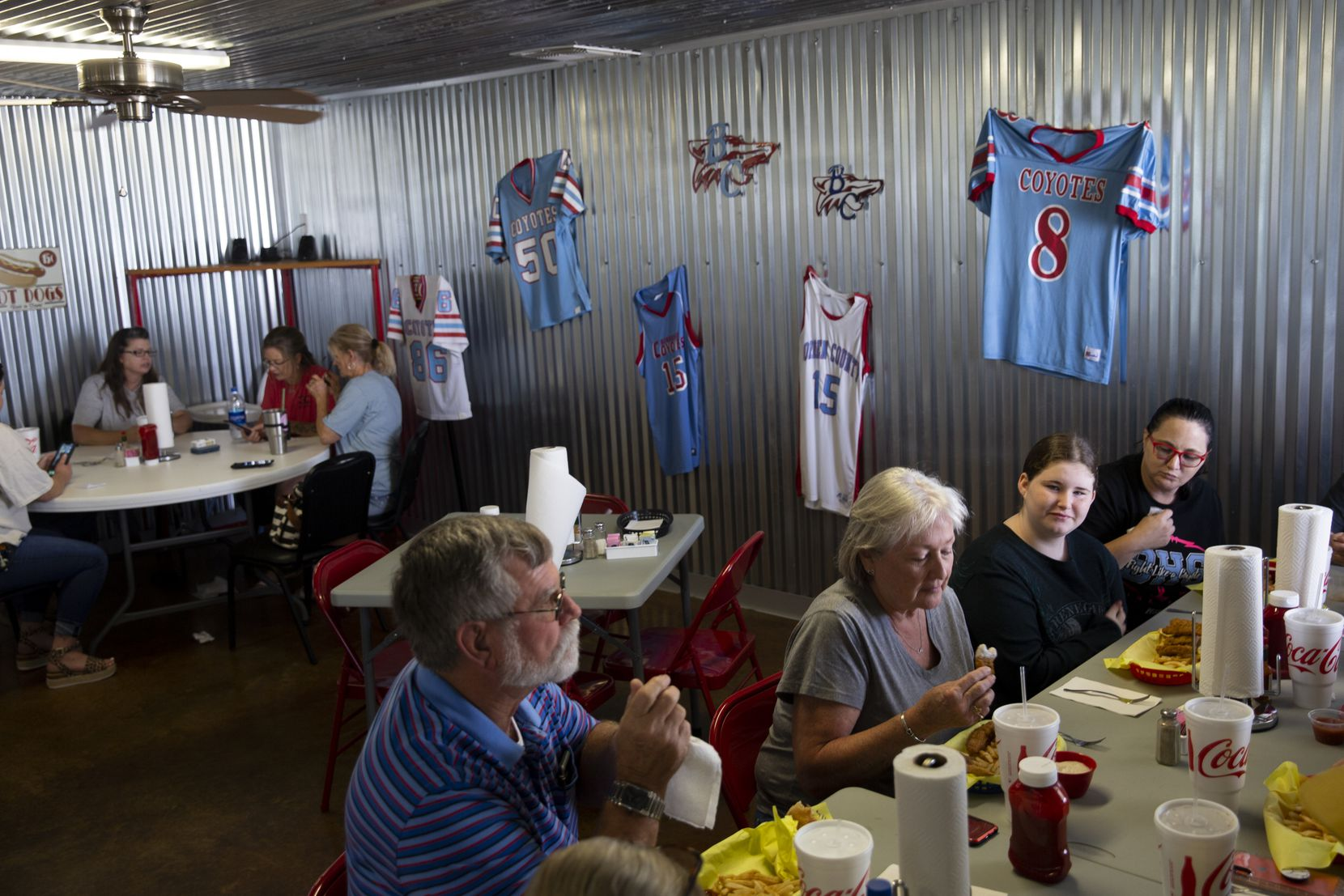 Borden County High School football jerseys hang in the background at The Blue Paw Cafe as Borden County Judge Ross Sharp (bottom left) enjoys lunch on Aug. 18, 2020 in Gail. There have been no reported cases of coronavirus in Borden County.