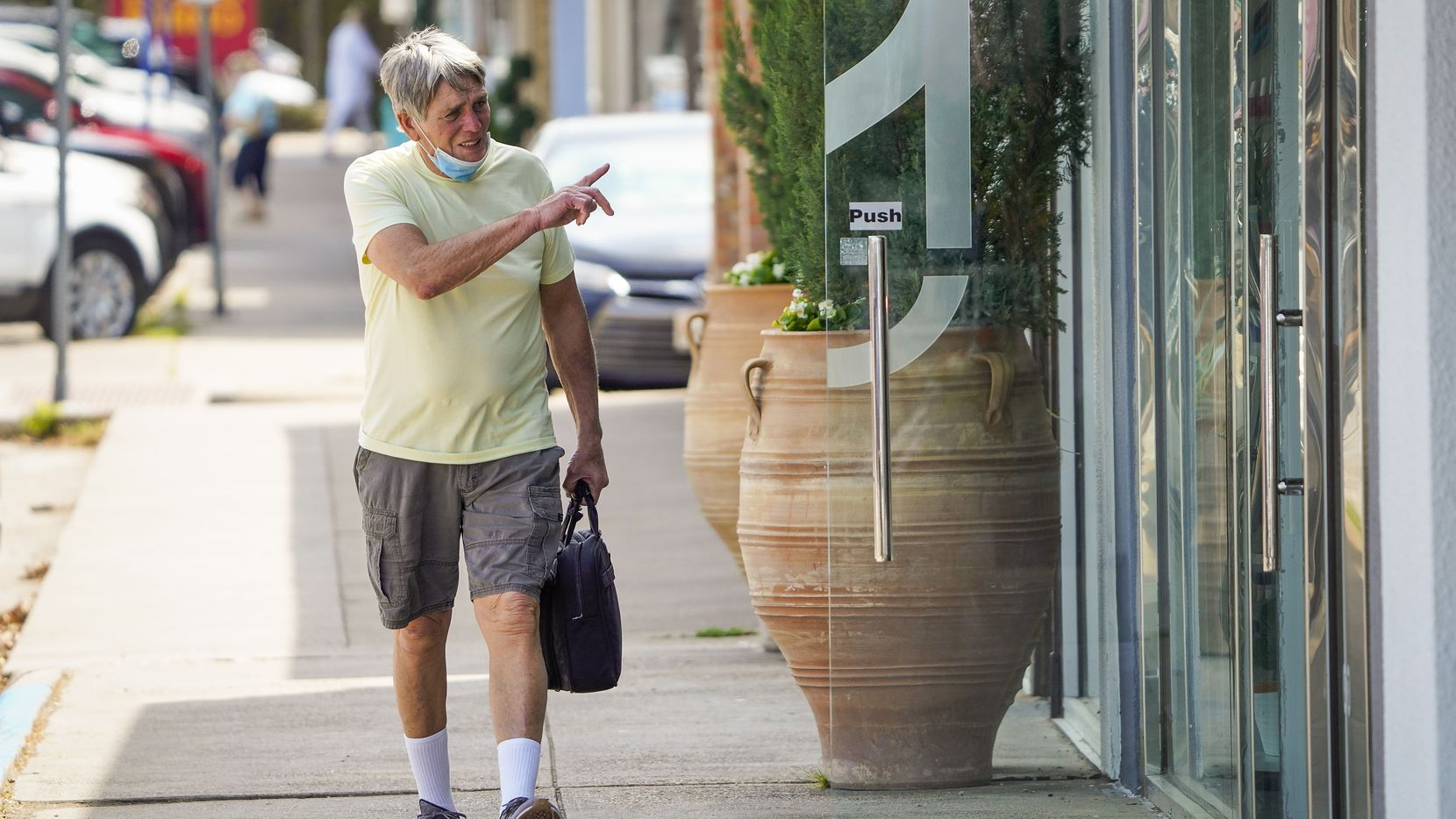 Vic Colon waves to people inside a business along Lovers Lane during his daily walk.