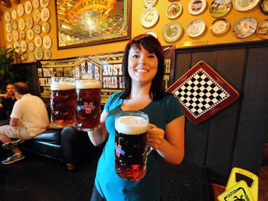 Flying Saucer on Belt Line Road in Addison is closing Dec. 31, 2020. Here, Kaylyn Steward carried mugs to thirsty customers at the beer-hoisting competition in 2014.