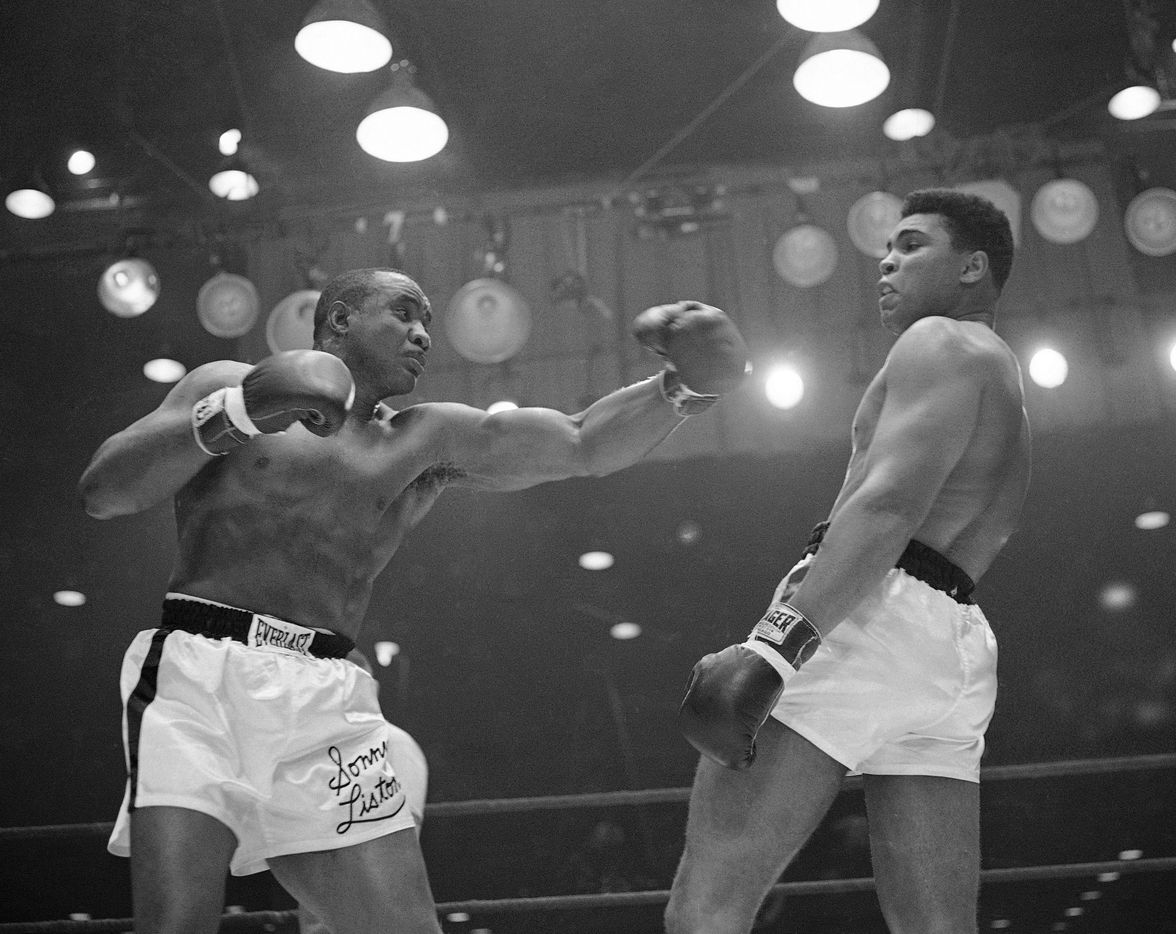 In this Feb. 26, 1964 file photo, Muhammad Ali (Cassius Clay)  uses a variety of bobbing and weaving to stay clear of the left arm of Sonny Liston in their title fight in Miami Beach, Fla.