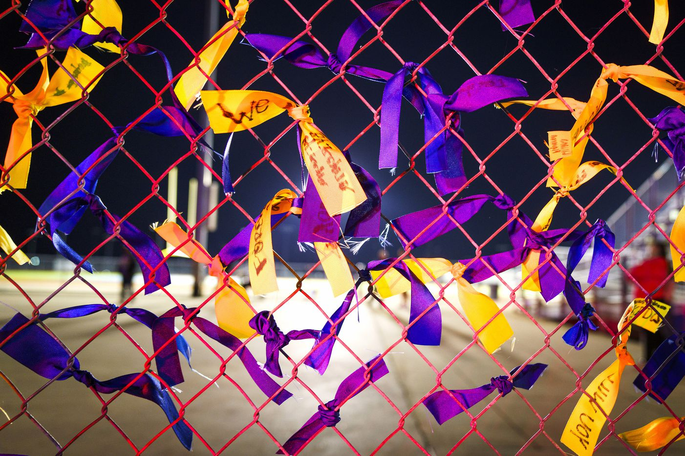 Ribbons in memory of  four students who were killed in a two-vehicle crash Tuesday fill the fence of the Community ISD football stadium following a vigil on Wednesday, Nov. 6, 2019, in Nevada, Texas.