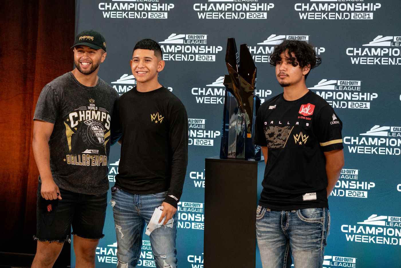 """From left, Steven Quevedo, Gabriel Castro, and Xavier Castro, brothers of Dallas Empire player Anthony """"Shotzzy"""" Cuevas-Castro, stand next to the Call of Duty league trophy before the start of the winners final between the Empire and the Atlana FaZe at the Galen Center on Saturday, August 21, 2021 in Los Angeles, California.  (Justin L. Stewart/Special Contributor)"""