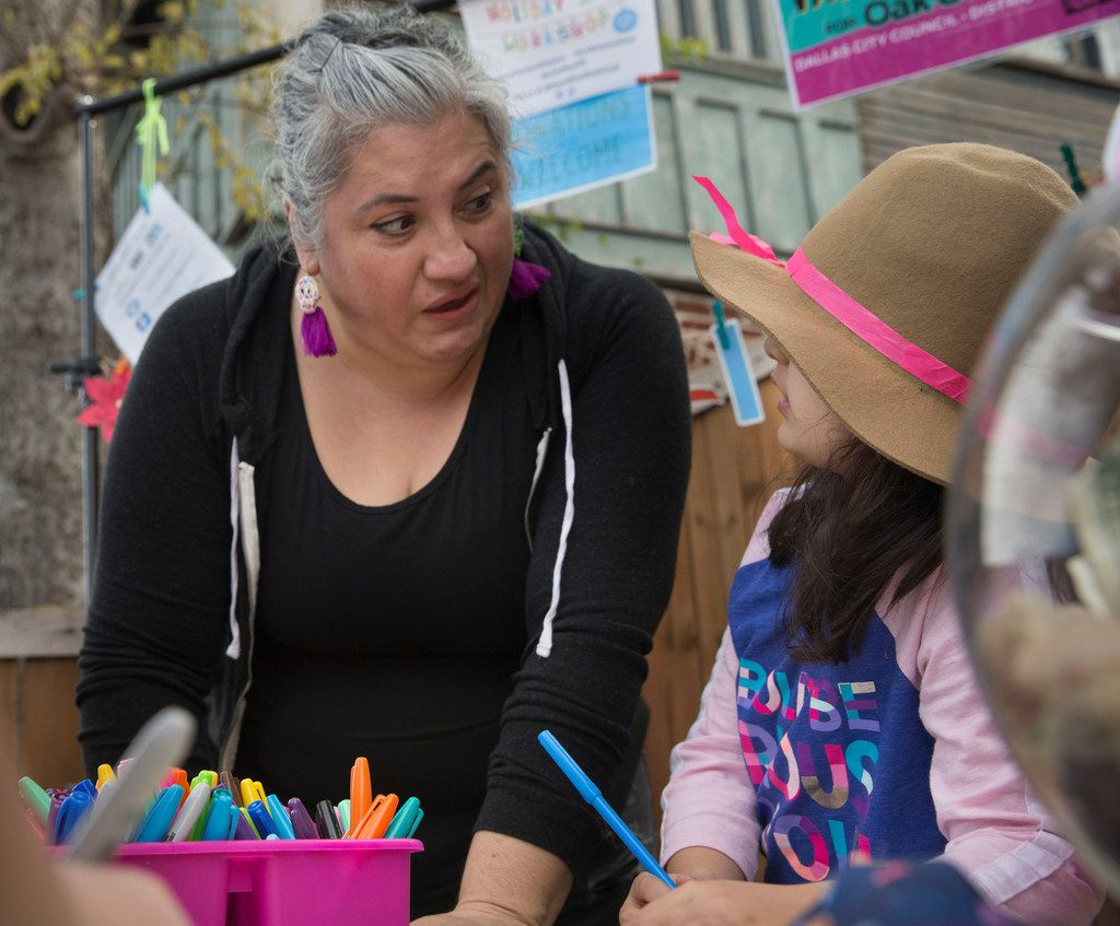 Ofelia Faz-Garza helps her daughter, Paloma Garza, 7, write a letter at the booth she was running at an arts bazaar  at the CocoAndre Chocolatier in Oak Cliff on Nov. 24, 2018.