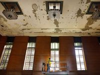 Contractors from Phoenix 1 Restoration have begun scraping loose paint in the East Texas Room where water damaged the Hall of State building at Fair Park in Dallas.