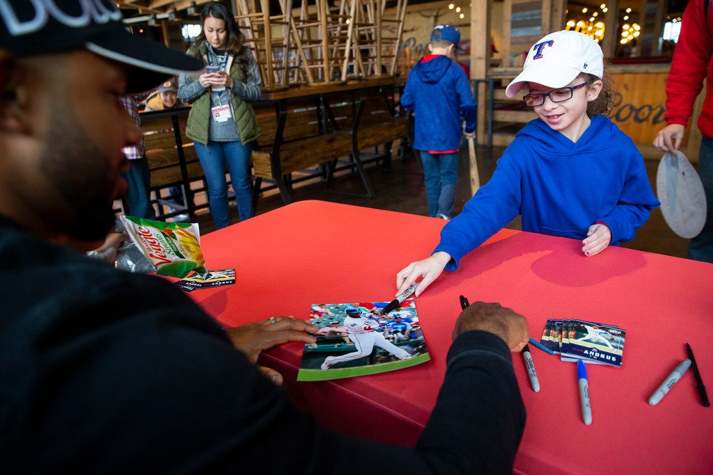 Bevin Thorpe, 8, from Forney gives Texas Rangers shortstop Elvis Andrus (1) a photo to sign during the Rangers' Peek at the Park fanfest on Jan. 25, 2020 in Arlington. Bevin said she felt shy but excited to meet Andrus. (Juan Figueroa/ The Dallas Morning News)