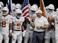 Texas head coach Tom Herman, center, prepares to takes the field with quarterback Sam Ehlinger (11) and the rest of the team during the first half of an NCAA college football game against Rice Saturday, Sept. 14, 2019, in Houston.