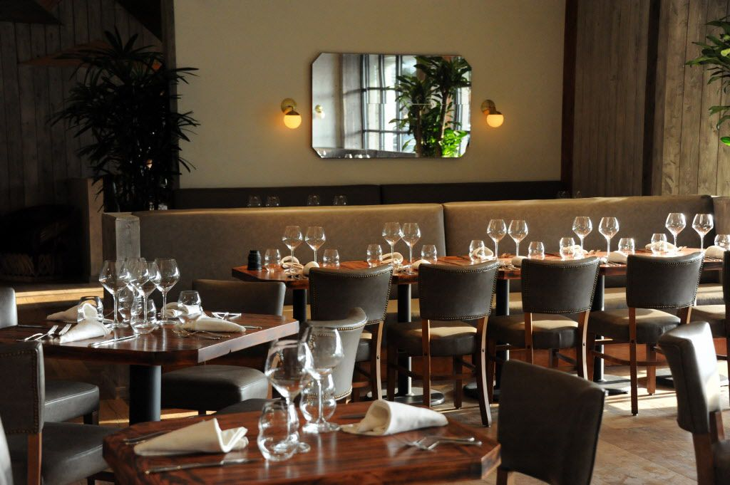 The dining room features ash wood tables, modern lighting, and wide windows at Madrina.