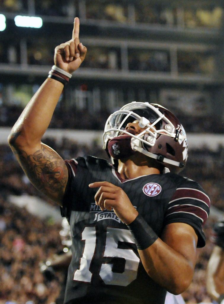 Mississippi State quarterback Dak Prescott (15) points skyward in remembrance of his mother after scoring a touchdown during the first half of an NCAA college football game against Kentucky in Starkville, Miss., Saturday, Oct. 24, 2015.
