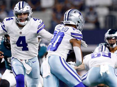 Dallas Cowboys quarterback Dak Prescott (4) hands the ball off to running back Tony Pollard (20) during the second quarter against the Philadelphia Eagles at AT&T Stadium in Arlington, Monday, September 27, 2021.