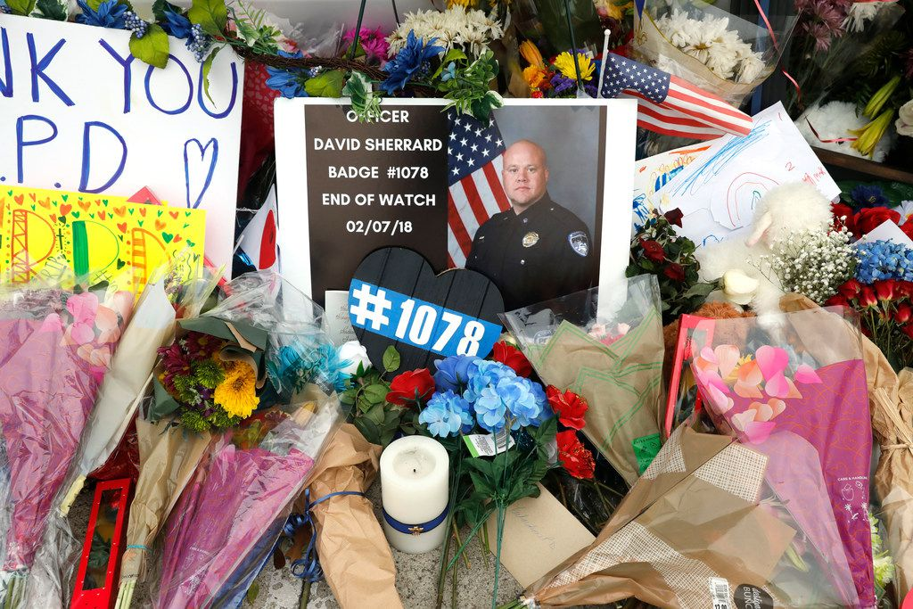 Flowers and other items were placed on a police cruiser at the Richardson police headquarters Monday, Feb. 12, 2018. Richardson officer David Sherrard was fatally shot Wednesday, Feb. 8 at an apartment complex.