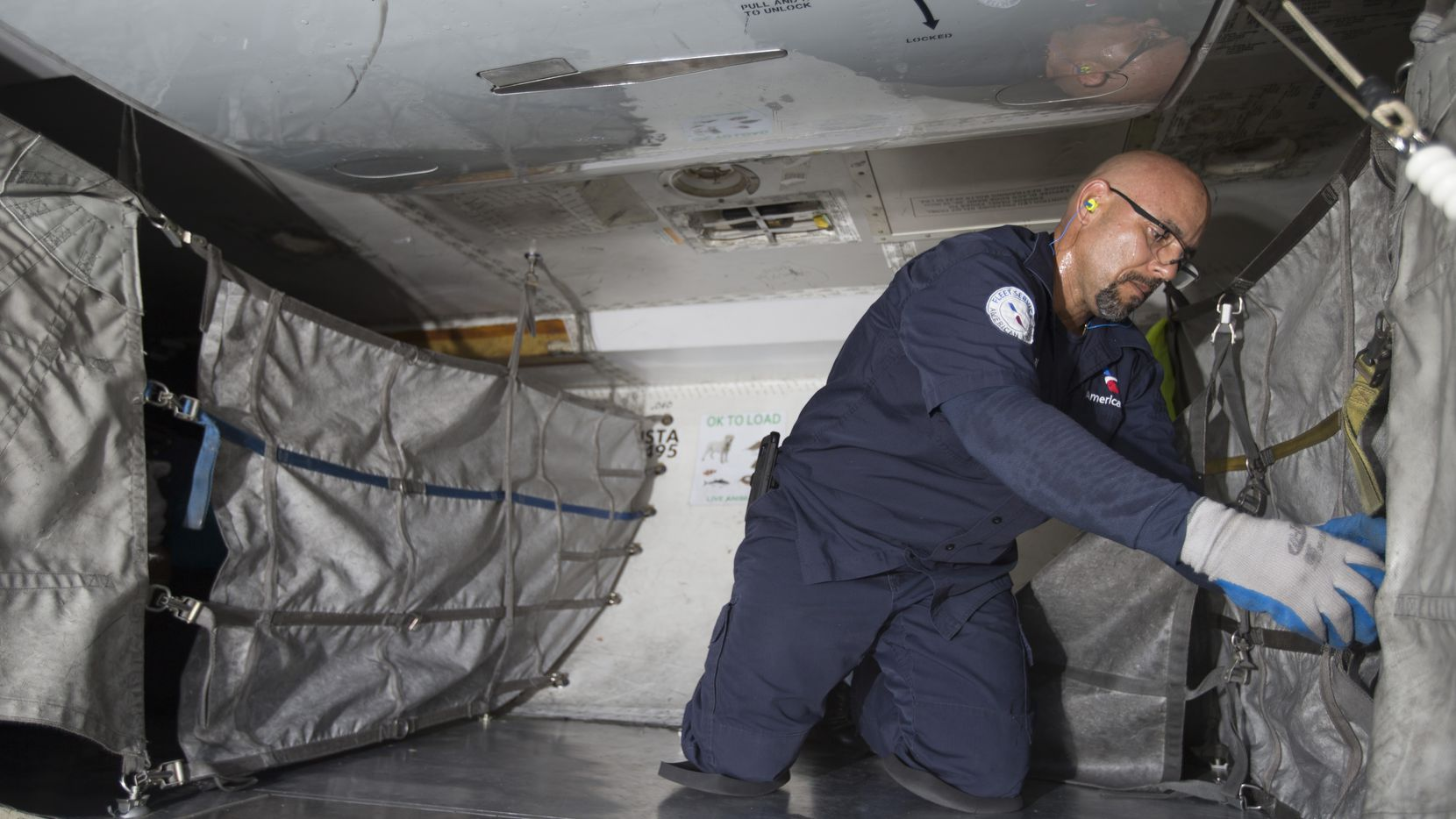 An American Airlines fleet worker loads cargo onto a plane.
