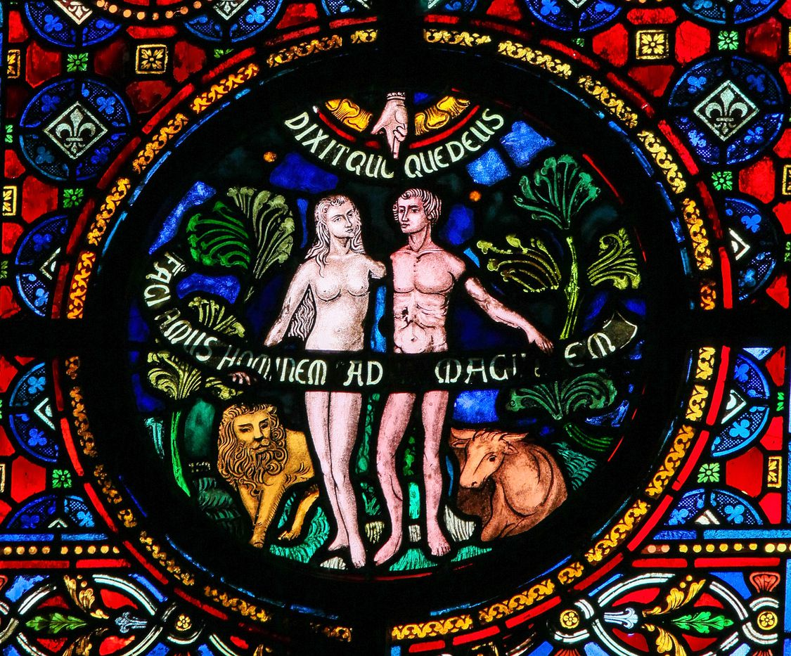 Dinant, Belgium - Oct. 16, 2011: Creation of Adam and Eve, stained glass window in the church of Dinant, Belgium.