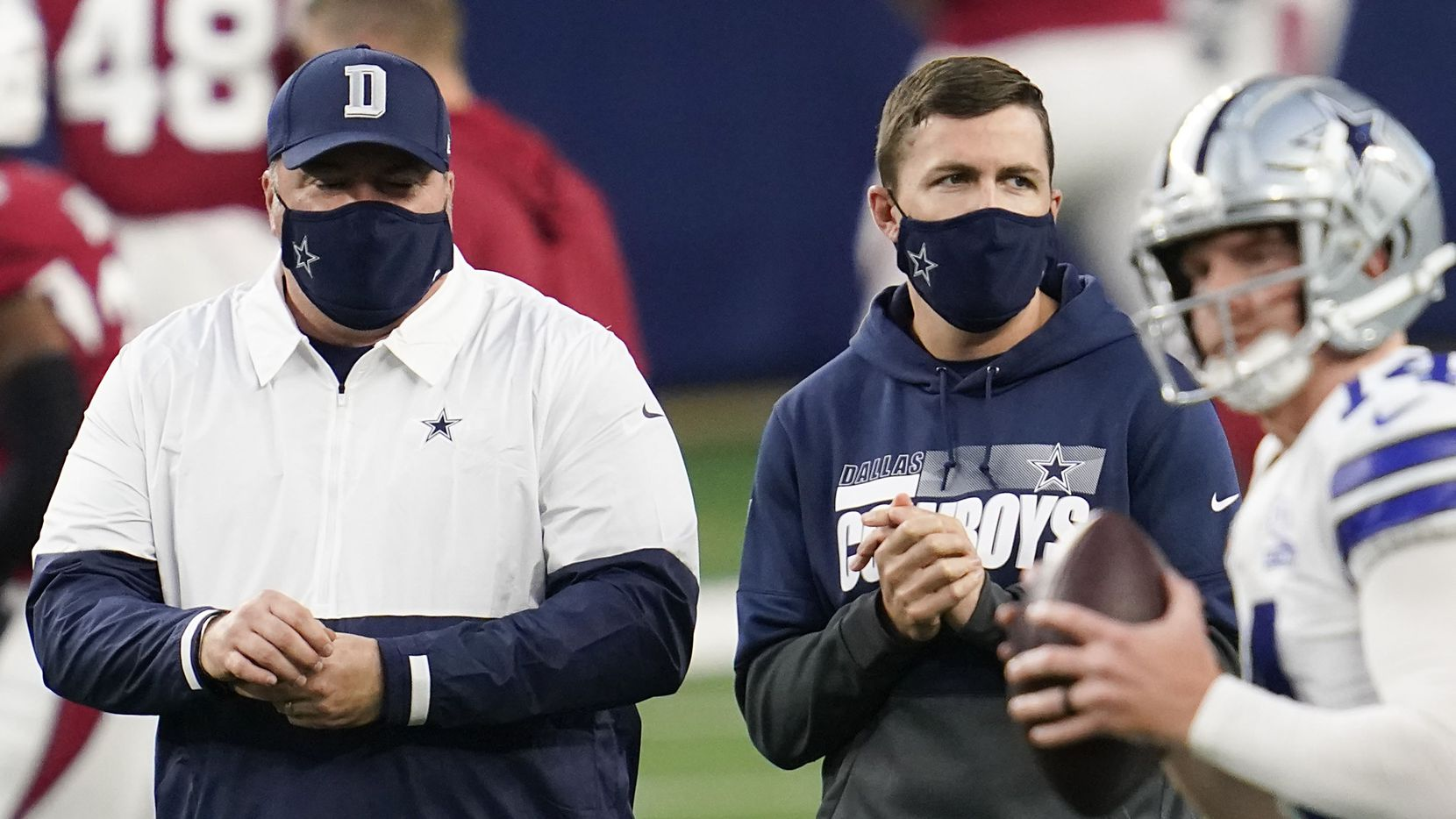 Dallas Cowboys head coach Mike McCarthy (left) and offensive coordinator coach Kellen Moore watch quarterback Andy Dalton warm up before an NFL football game against the Arizona Cardinals at AT&T Stadium on Monday, Oct. 19, 2020, in Arlington.