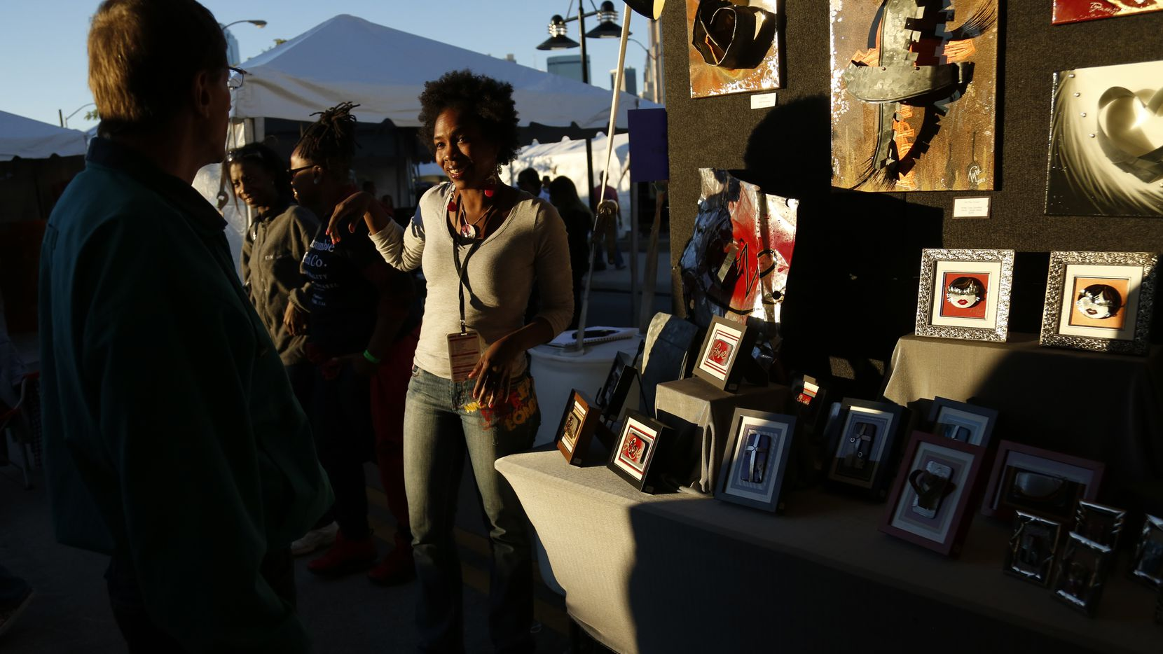 Artist Tyra Goodley, background center, talks with visitors at her booth during the Lamar Street Festival in Dallas, TX on October 19, 2013.