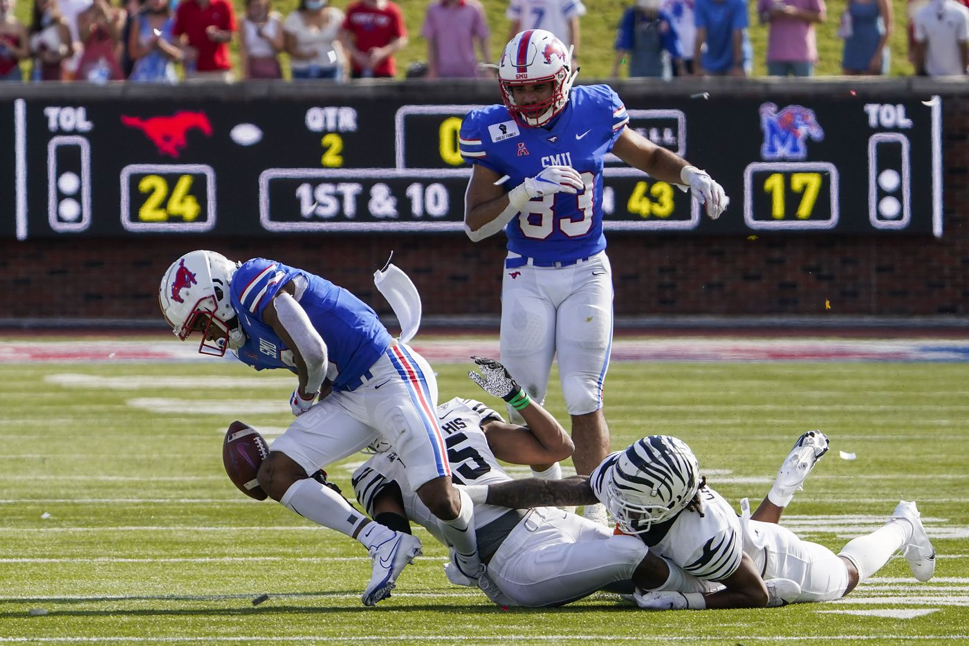 SMU wide receiver Reggie Roberson Jr. (8) turns the ball over with a fumble after a hit from Memphis defensive back Quindell Johnson (15) and defensive back T.J. Carter (2) during the first half of an NCAA football game at Ford Stadium on Saturday, Oct. 3, 2020, in Dallas.